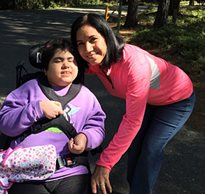A mom leans over to take a picture with her daughter in a wheelchair on a trail at an inclusion camp