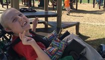 A young boy with special needs in a wheelchair on the playground at a park traveling for a field trip