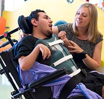 A disability advocate helps a patient tilt their chair back so they can make eye contact
