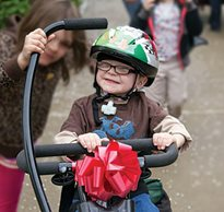 A young boy grins as he rides his adaptive tricycle from the Great Bike Giveaway