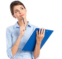 A therapist with a clipboard in hand holds a pencil to her mouth as she looks off thinking about what to write