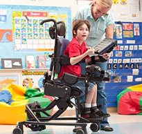 A therapist assists a child in adaptive chair using a computerized screen to practice motor learning tasks