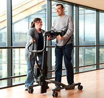 A smiling therapist at a rehab facility helps an adult patient with complex disabilities walk in a TRAM device