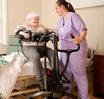 A caregiver using the Rifton TRAM to help an elderly homecare client make a seated transfer into bed.