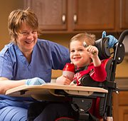 A therapist with a young boy using the Rifton Activity Chair for feeding positioning