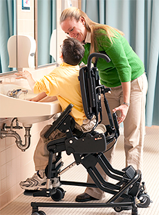 A therapist activates the Rifton Activity Chair's tilt-in-space feature to allow a school-aged boy to wash his hands at a sink
