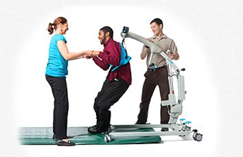 The SoloLift in action, lifting a man with developmental disabilities from a mat on the floor into a standing position