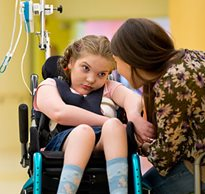 A Pediatric Life Care Planner positions a young girl with special needs in her adaptive equipment